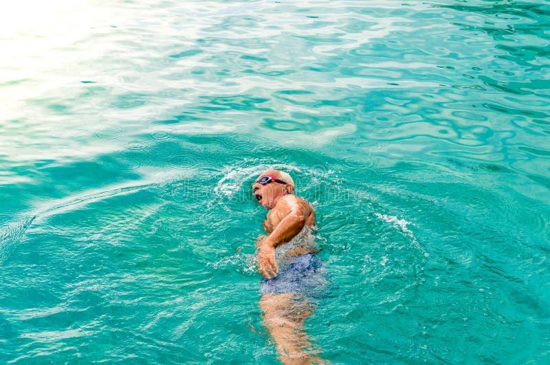 Opinión superior el hombre caucásico joven que nada arrastre delantero en una piscina foto de archivo libre de regalías