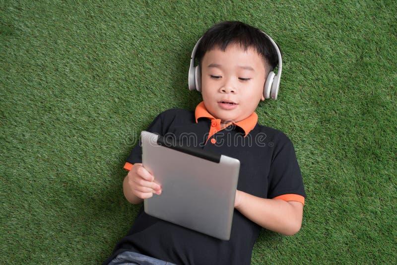 Opini?n superior el ni?o peque?o en auriculares usando una tableta digital y la sonrisa mientras que miente en hierba verde fotografía de archivo