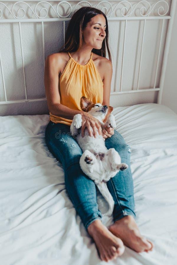 Opinión superior el perro cara arriba en la mentira en las piernas de una mujer que tienen un rato bueno y de la diversión imagen de archivo