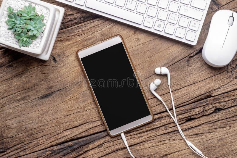 Opinión superior el smartphone, auriculares, el teclado y el ratón en blanco en la mesa de madera del grunge Mofa plana de la end fotos de archivo