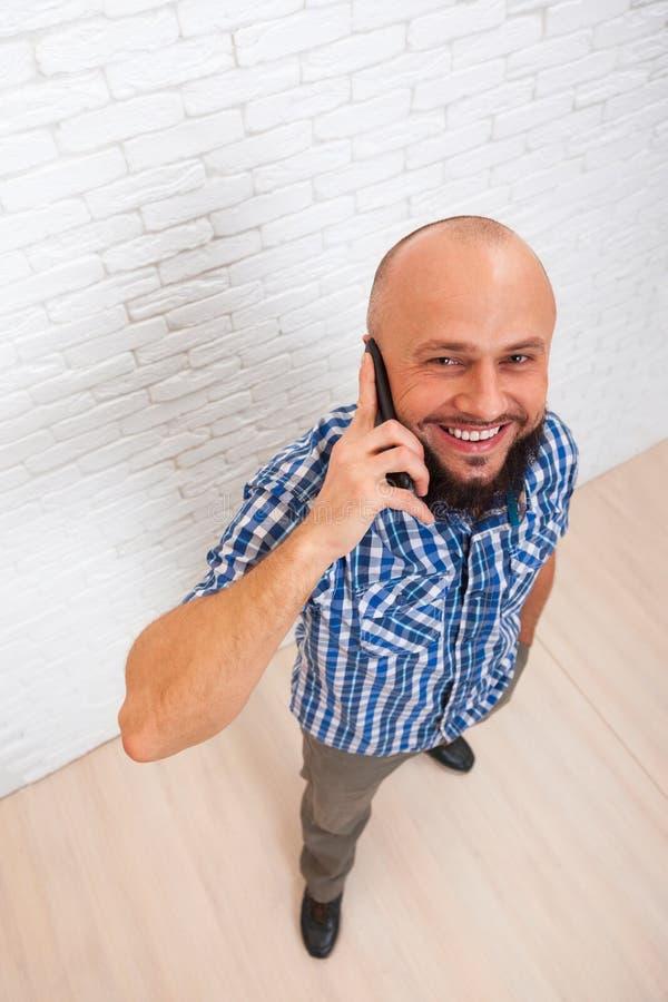 Opinión superior elegante de la llamada de teléfono de negocios de la célula barbuda casual del hombre fotos de archivo
