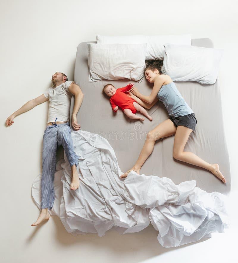 Opinión superior la familia feliz con un niño recién nacido en dormitorio fotos de archivo