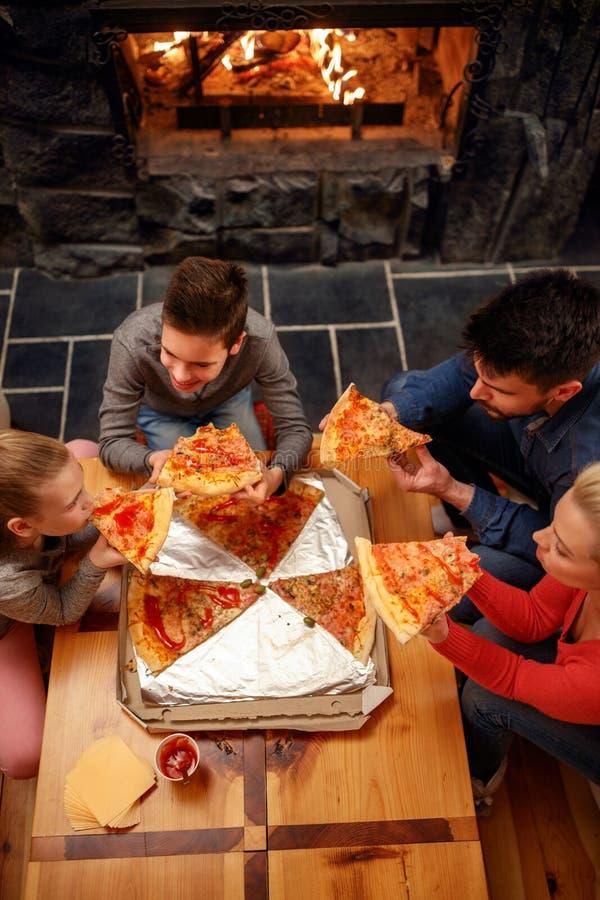 Opinión superior la familia feliz que come la pizza fotografía de archivo libre de regalías