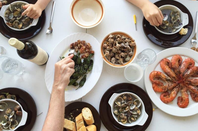 Opinión superior la familia que come los mariscos alrededor de una tabla blanca del alto ángulo de visión imagenes de archivo