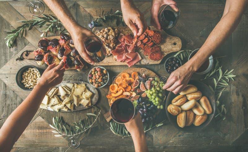 Opinión superior la gente que bebe, comiendo junto y sosteniendo los vidrios foto de archivo