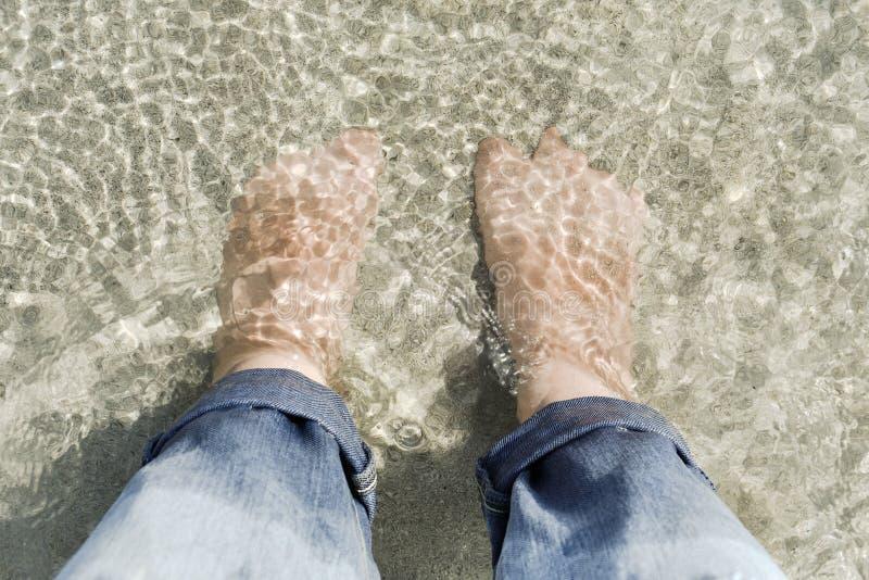Opinión superior la gente que mira abajo los pies puestos debajo de la arena y del mar fotografía de archivo