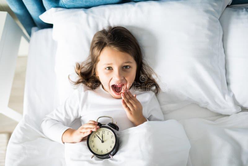 Opinión superior la muchacha alegre que miente en cama con el despertador en casa, mirando la cámara fotografía de archivo