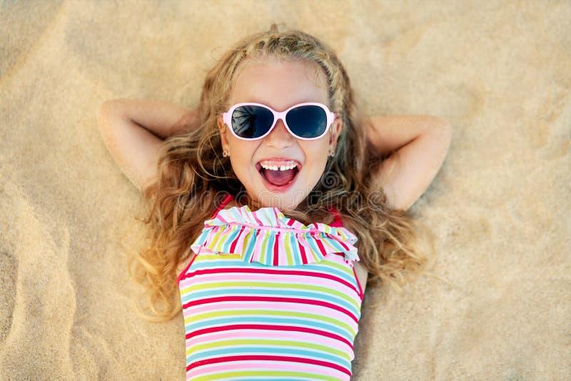Opinión superior la muchacha rubia bastante pequeña en las gafas de sol que mienten en la playa arenosa durante vacaciones de ver imágenes de archivo libres de regalías