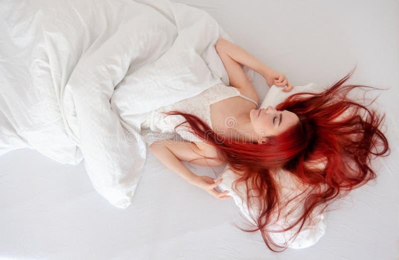Opinión superior la mujer atractiva, joven, pelirroja que se relaja en la cama, gozando de las hojas suaves frescas en dormitorio imagenes de archivo