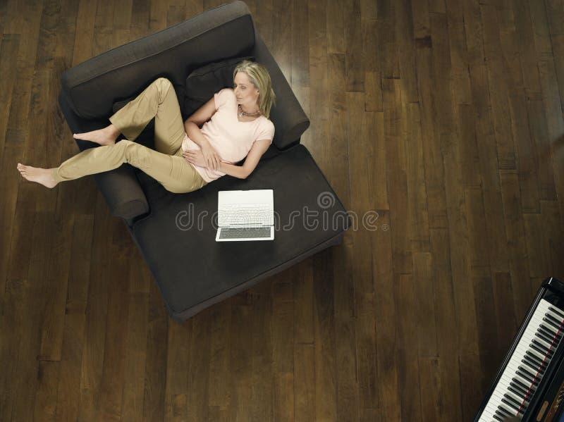 Opinión superior la mujer con el ordenador portátil que duerme en el sofá imagenes de archivo