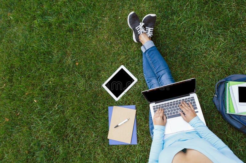 Opinión superior la mujer con el ordenador portátil que se sienta en la hierba verde foto de archivo