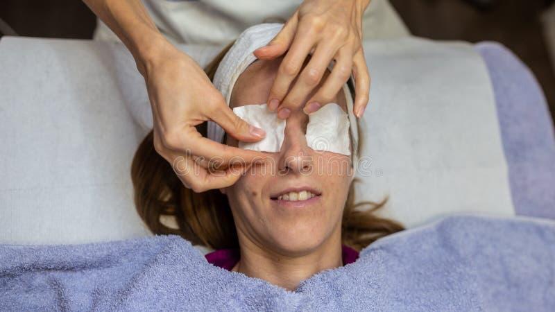Opinión superior la mujer joven que miente en la tabla del masaje que consigue un masaje facial foto de archivo libre de regalías