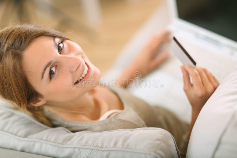 Opinión superior la mujer que hace compras en línea de hogar foto de archivo