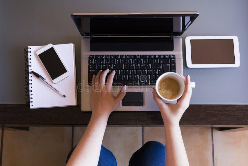 Opinión superior la mujer que trabaja en el ordenador portátil con la taza de café, smartpho imagen de archivo