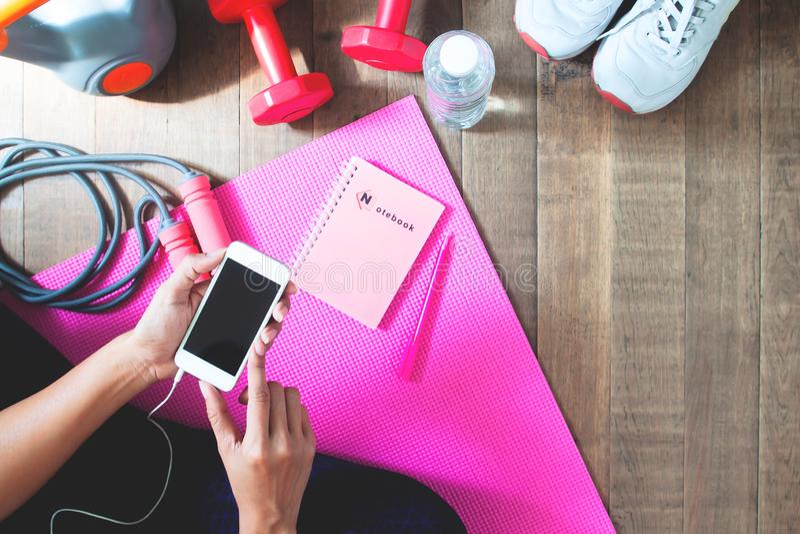 Opinión superior la mujer que usa el teléfono móvil para el entrenamiento en línea de la aptitud imagen de archivo libre de regalías