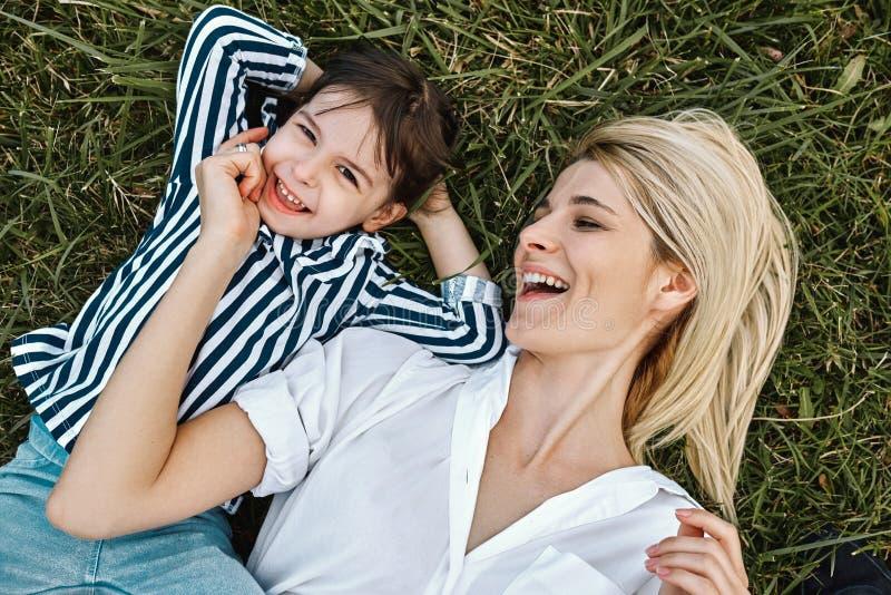 Opinión superior la mujer rubia feliz que sonríe y que juega con su pequeño niño lindo, mintiendo en la hierba verde al aire libr foto de archivo