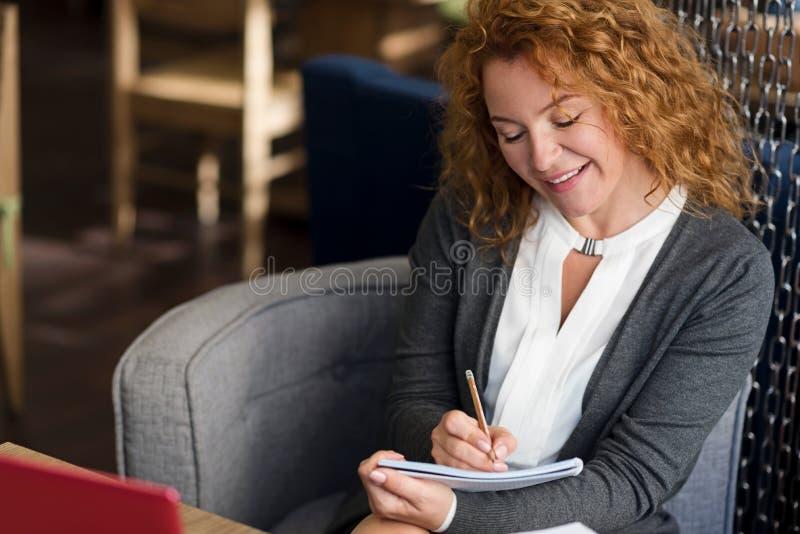 Opinión superior la mujer sonriente que toma notas foto de archivo