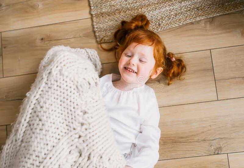 Opinión superior la pequeña princesa linda del pelirrojo que juega en piso en casa imagen de archivo libre de regalías