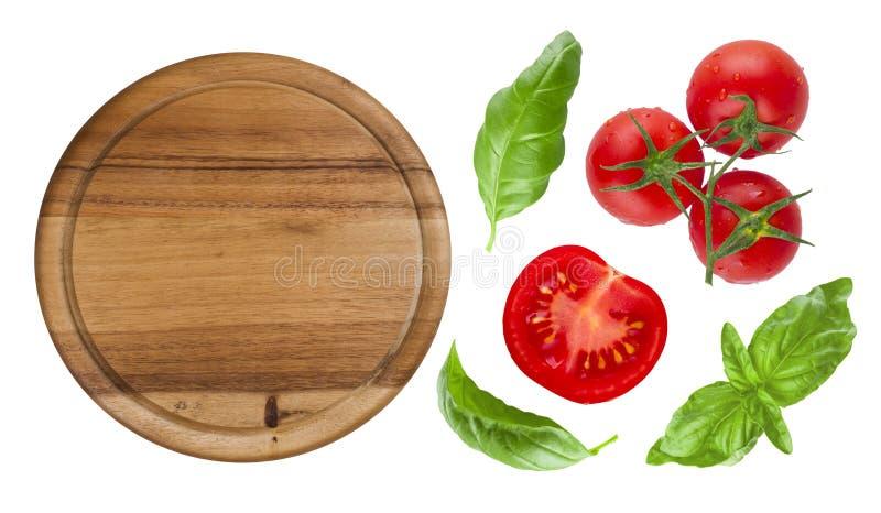 Opinión superior la tabla de cortar aislada con el tomate y la albahaca fotografía de archivo libre de regalías