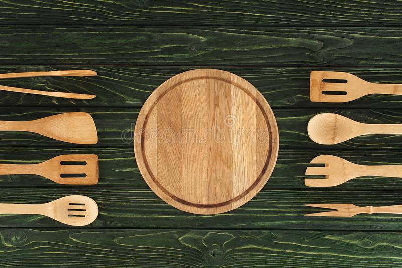 opinión superior la tabla de cortar redonda entre los utensilios de la cocina fotos de archivo libres de regalías