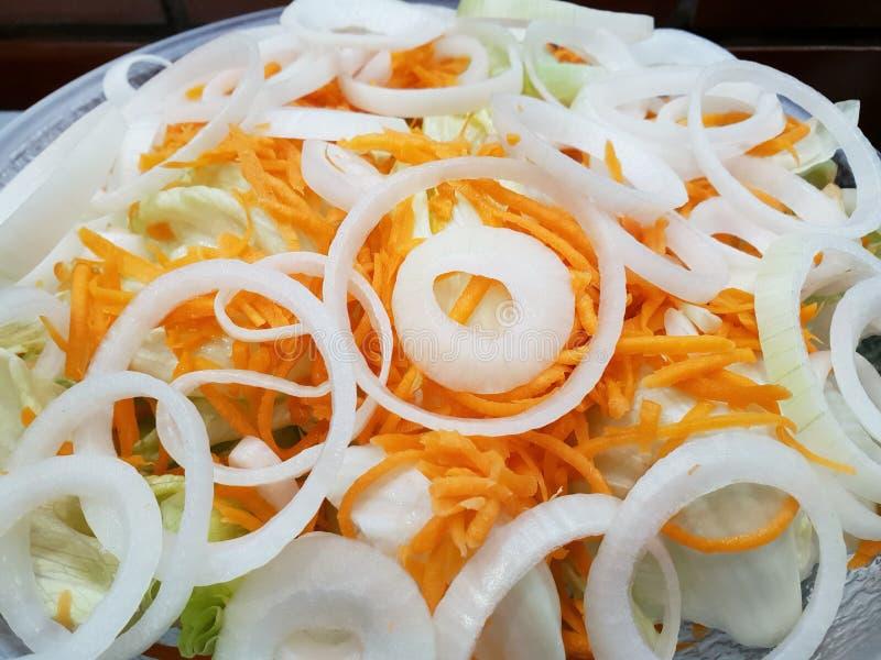 Opinión superior las verduras frescas mezcladas con las rebanadas de la lechuga, de la zanahoria y de la cebolla para cocinar o l foto de archivo