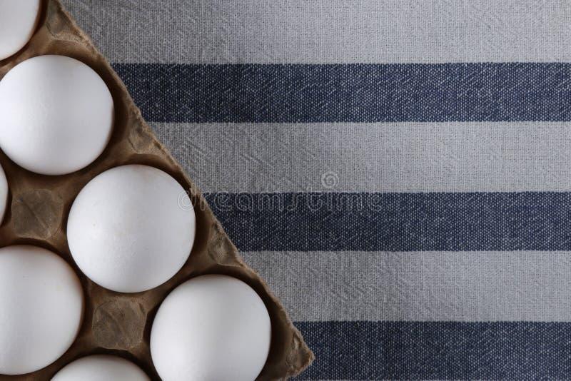 Opinión superior llena de los huevos blancos sobre fondo ligero de la materia textil imágenes de archivo libres de regalías