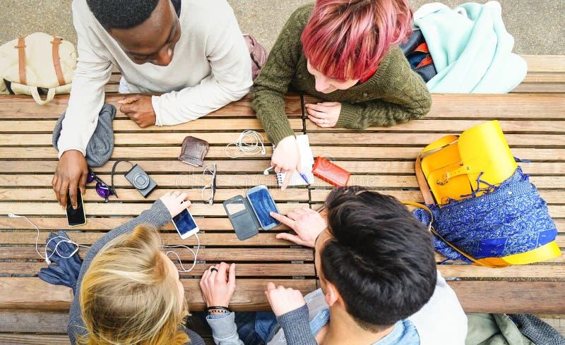 Opinión superior los amigos multirraciales que usan el teléfono elegante móvil foto de archivo libre de regalías