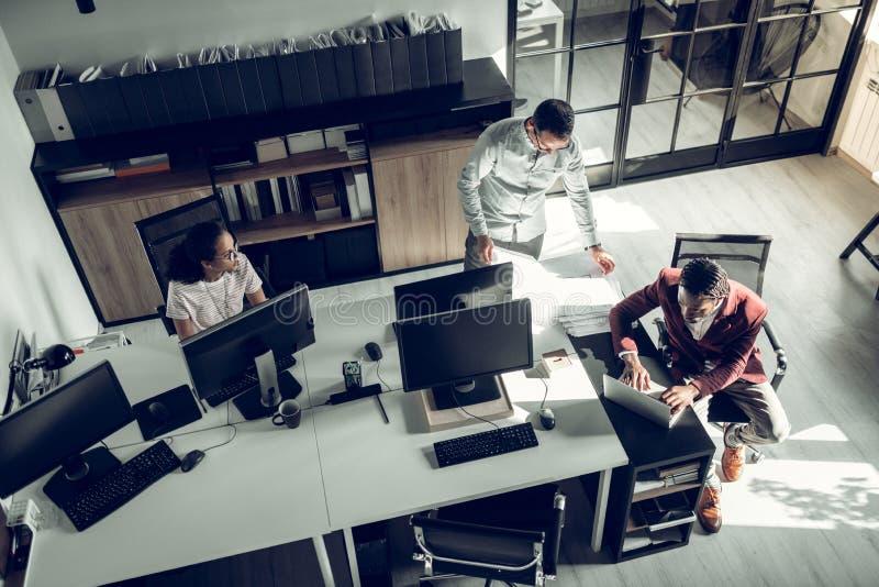 Opini?n superior los hombres de negocios que trabajan en el equipo en oficina espaciosa foto de archivo libre de regalías