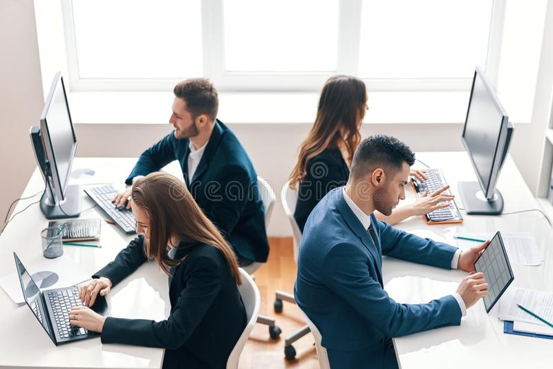 Opinión superior los hombres de negocios que trabajan en el ordenador en oficina moderna foto de archivo