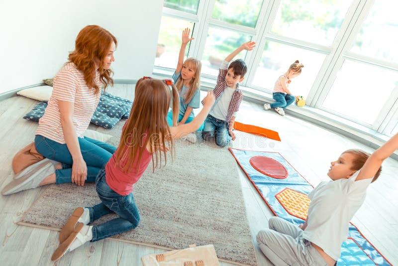 Opinión superior los niños bonitos agradables que aumentan sus manos imagenes de archivo