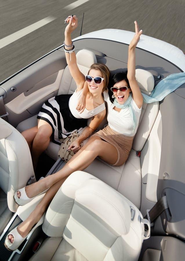 Opinión superior mujeres en el coche con sus manos para arriba imagenes de archivo