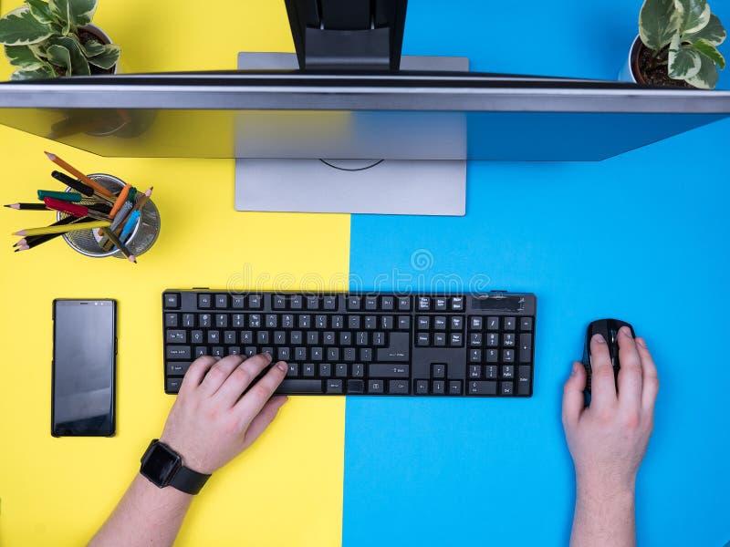 Opinión superior puesta plano el hombre que se sienta en su oficina que mecanografía en el teclado imagen de archivo