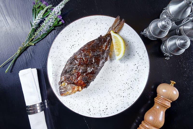Opinión superior sobre dorado servido de los pescados en la placa blanca Fondo oscuro Mariscos para el almuerzo Copie el espacio  foto de archivo