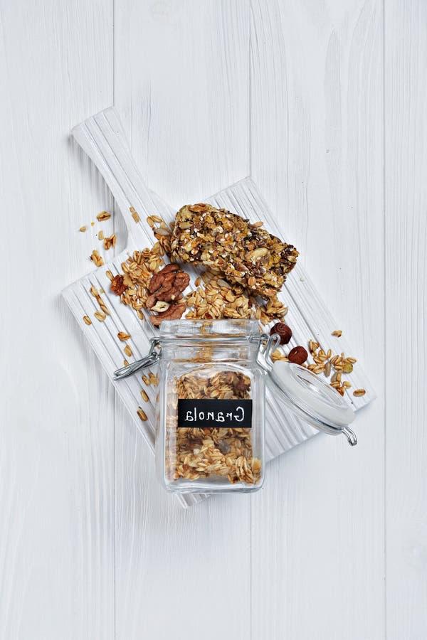 Opinión superior sobre el granola hecho en casa del desayuno sano con las nueces y las semillas de girasol en barra de cristal ab foto de archivo