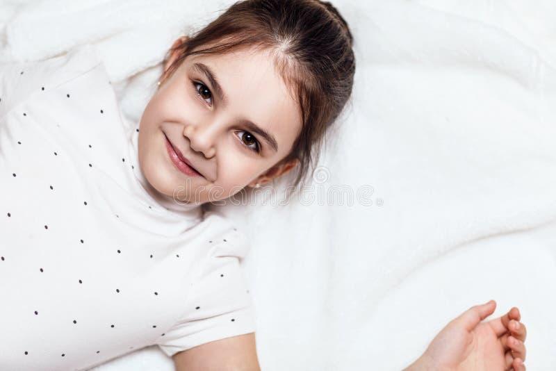 Opinión superior sobre la muchacha morena linda que miente en cama fotografía de archivo libre de regalías