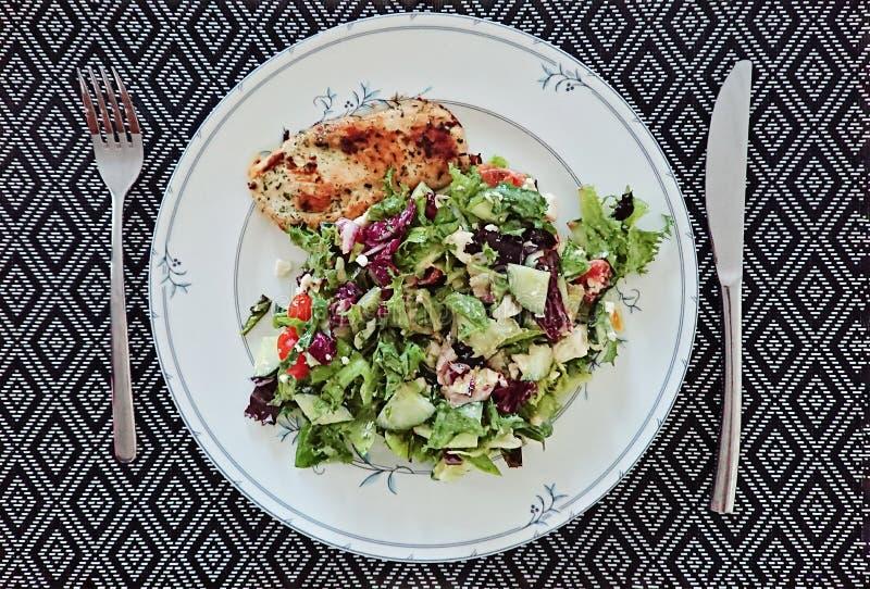 Opini?n superior sobre la placa con la ensalada y verduras frescas, prendedero del pollo y vajilla imagen de archivo libre de regalías
