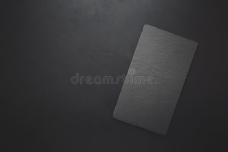 Opinión superior sobre la placa de la pizarra del negro del rectángulo en fondo oscuro rústico Copie el espacio entonado foto de archivo libre de regalías
