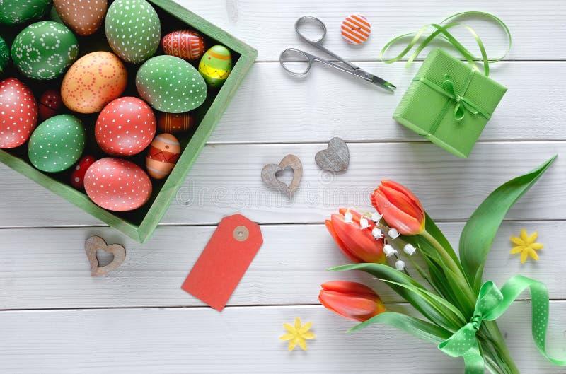 Opinión superior sobre la tabla de madera blanca con la caja de huevos de Pascua pintados, foto de archivo libre de regalías