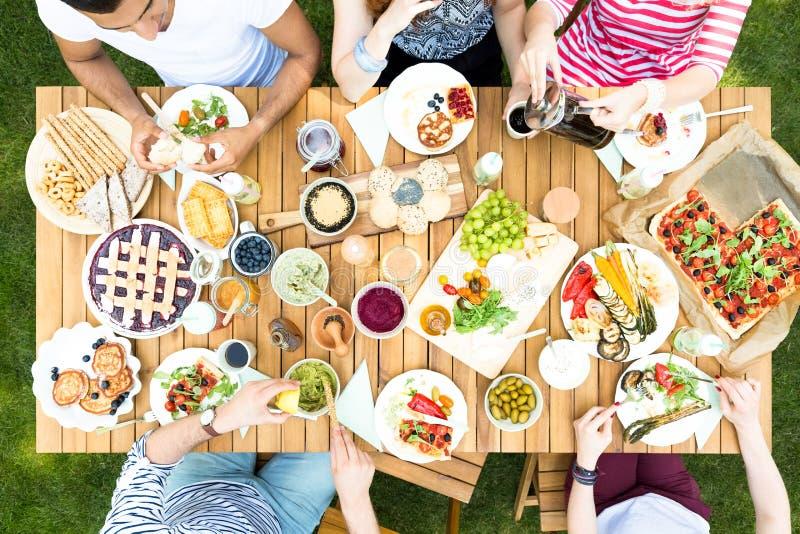Opinión superior sobre la tabla del jardín con la ensalada, las frutas y la pizza durante hacia fuera imagenes de archivo