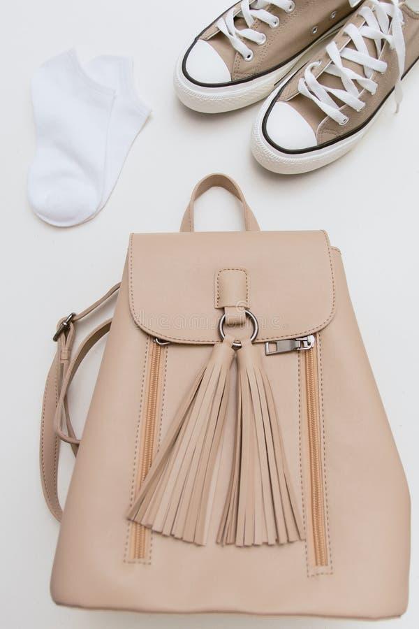Opinión superior sobre las zapatillas de deporte marrones, mochila beige, calcetines blancos en fondo en colores pastel foto de archivo