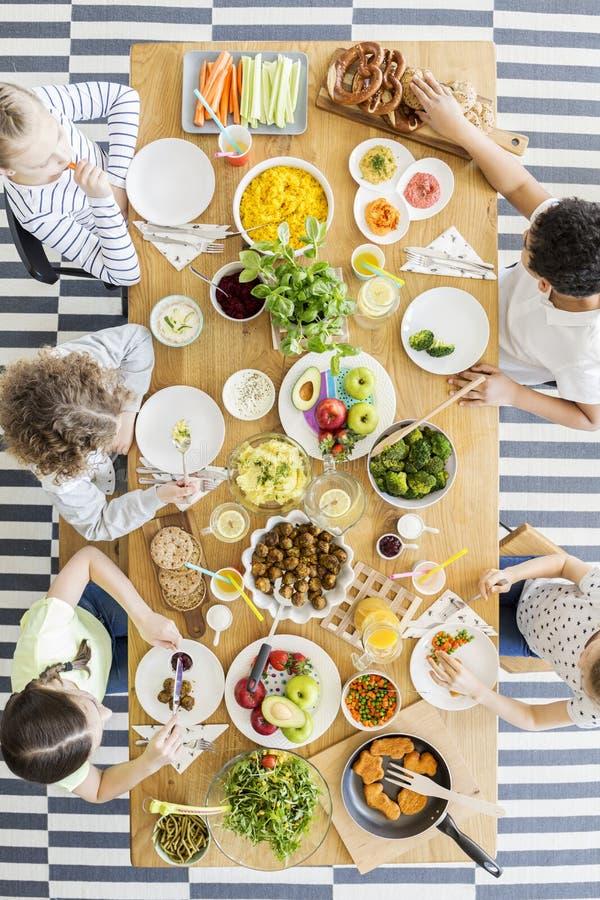 Opinión superior sobre los niños que comen la cena foto de archivo libre de regalías