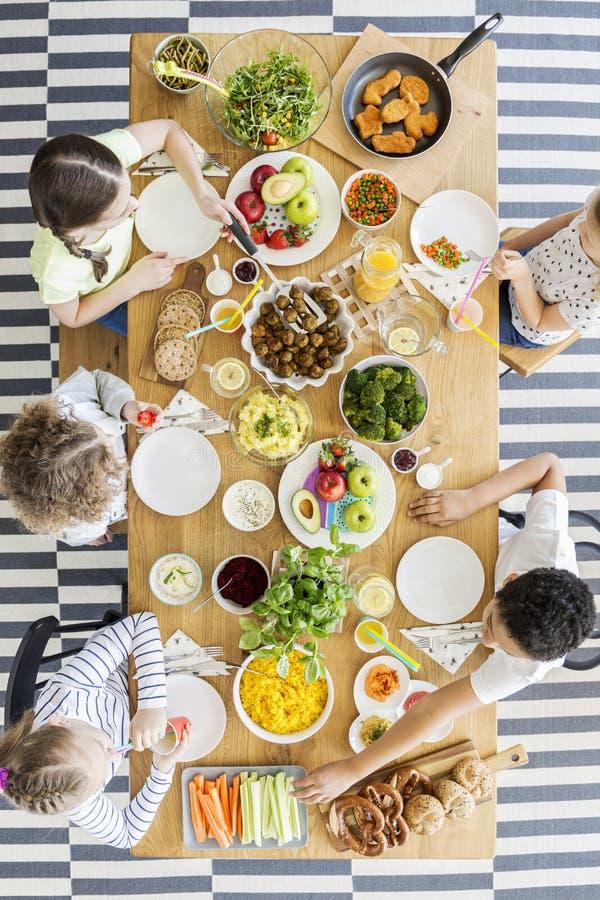 Opinión superior sobre los niños que comen la cena sana durante cumpleaños fotos de archivo libres de regalías