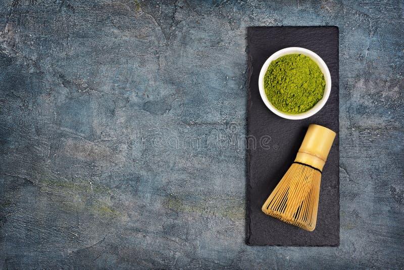 Opinión superior sobre polvo verde orgánico del ½ del ¿del teaï del matcha con el batidor de bambú en tablero negro de la pizarra imágenes de archivo libres de regalías