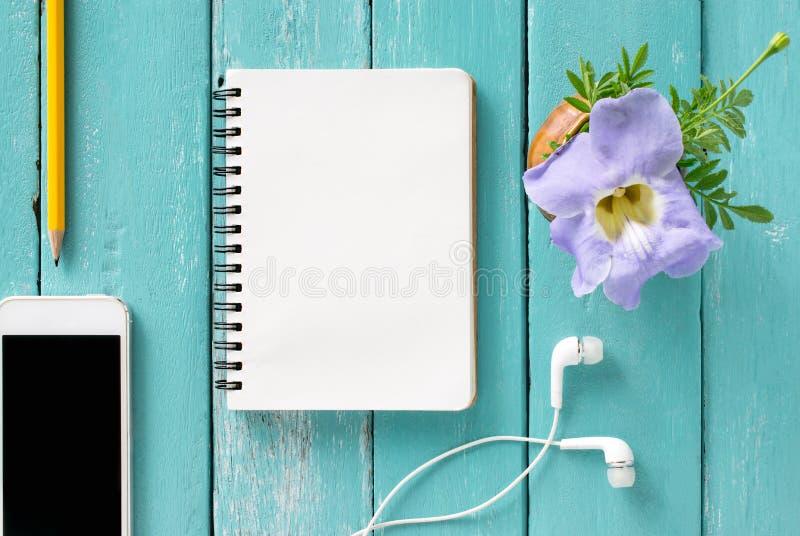 Opinión superior sobre un escritorio de madera con el smartphone, cuaderno, lápiz y fotos de archivo