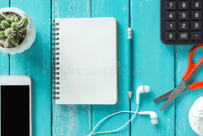 Opinión superior sobre un escritorio de madera con el smartphone, cuaderno, lápiz y imagen de archivo