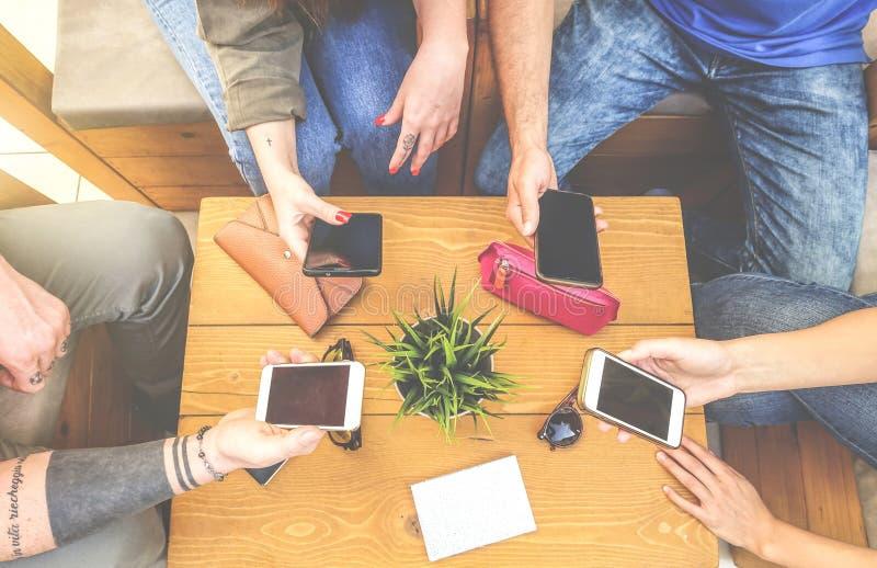 Opini?n superior un grupo de amigos del inconformista que se sientan en un caf? de la barra usando el tel?fono elegante m?vil - n fotografía de archivo