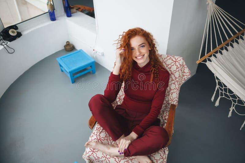 Opinión superior una mujer feliz sonriente que se sienta en una silla foto de archivo
