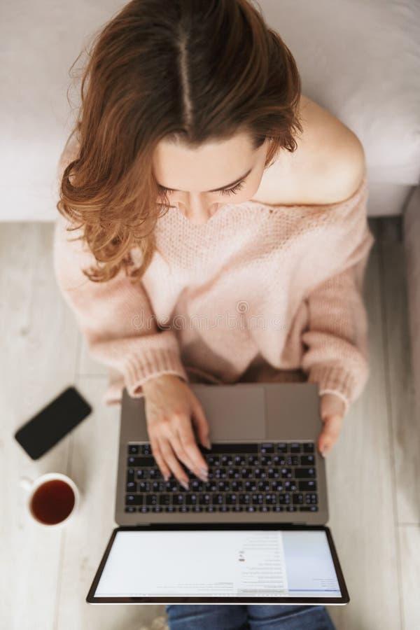 Opinión superior una mujer que trabaja en el ordenador portátil imagenes de archivo