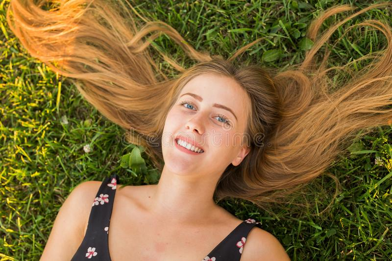 Opinión superior una mujer relajada feliz que miente en la hierba verde y la sonrisa fotografía de archivo libre de regalías