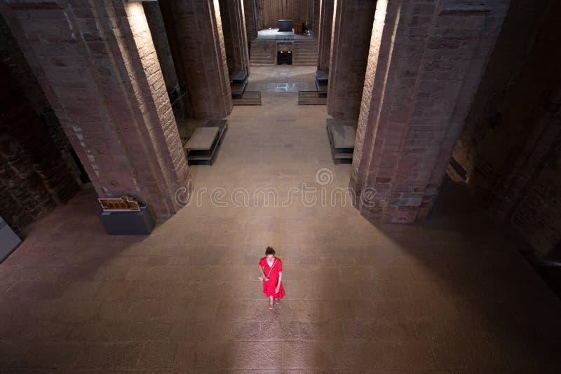 Opinión superior una mujer vestida roja dentro de la iglesia de Sant Vicente de Cardona en Cataluña, España fotos de archivo libres de regalías